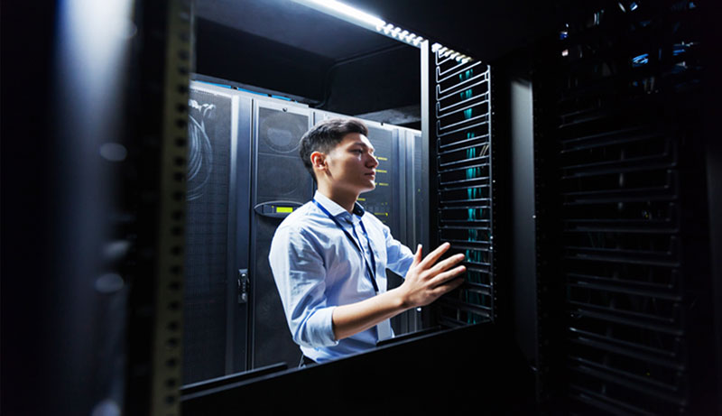 IT tech looking at server rack